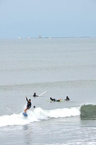 湘南海岸から海を眺めた烏帽子岩とサーファー