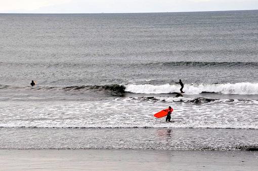 江ノ島片瀬海岸西浜で曇り空の下のサーファー