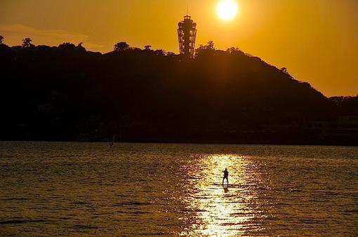 腰越漁港から片瀬東浜越しの江ノ島の夕日とパドルサーフィン